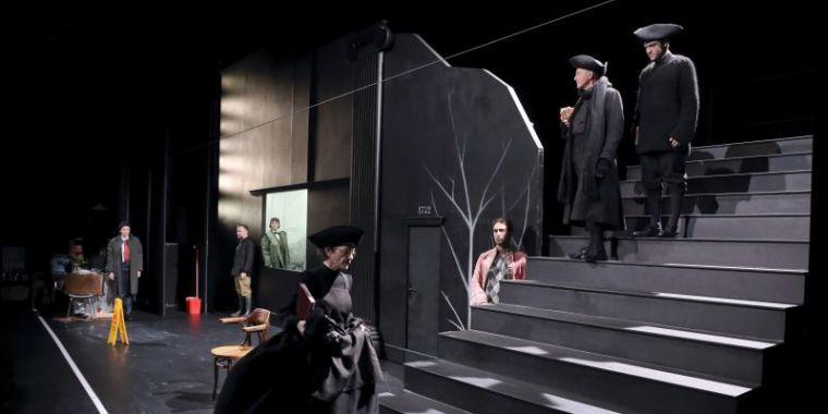 Décor sombre et géométrique, elle monte, sévère les marches des escaliers. 6 autres personnages la regardent