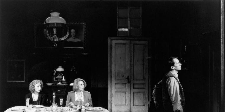 Deux femmes à table, un homme debout regarde loin devant