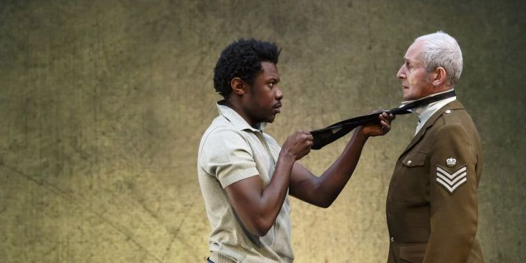 Un homme noir braque un officiuer blanc avec une carabine